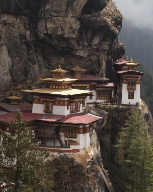 """Klasztor Taktsang (""""Tygrysie gniazdo""""), zawieszony nad doliną na skalnej półce. Takstang to jedno z najświętszych sanktuariów w Bhutanie, a spacer do niego zapewnia niezapomniane wrażenia. Miejscowi wierzą, że guru Rinpocze, główny krzewiciel buddyzmu tybetańskiego, przybył tu na grzbiecie tygrysa, by medytować."""