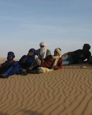 Tuerescy mezczyzni odpoczywajacy na Saharze na piasku - om tramping klub