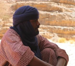 Portret tuareskiego mezczyzny na tle skal na Saharze - om tramping klub
