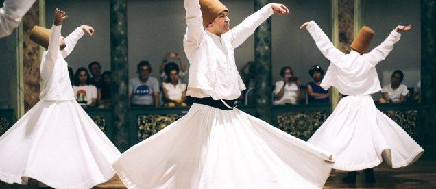 Trójka derwiszów w białych strojach podczas tańca
