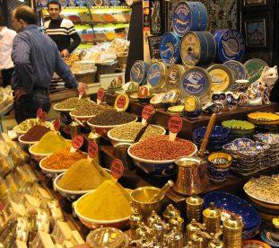 Stragan na bazarze w Stambule z puszkami kawioru, kolorową uzbecką ceramiką i przyprawami