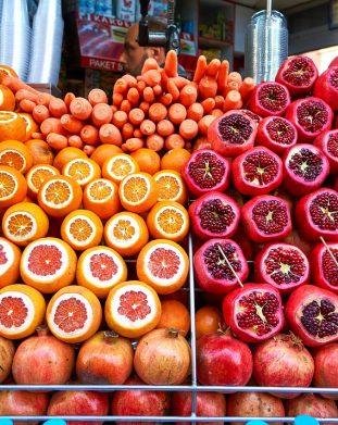 Soczyste pomarańcze, marchew i granaty na straganie na stambulskim bazarze