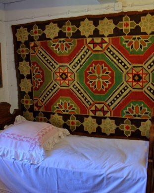 Wnętrze izby z drewnianym łóżkiem i kilimem na ścianie w skansenie w Sanoku