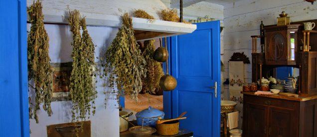 Tradycyjna kuchnia z piecem nad którymi wiszą suszone zioła w skansenie w Sanoku