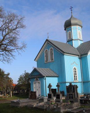 Błękitna zabytkowa cerkiewka z klasyczną kopułą na cmentarzu w Rybołtach na Podlasiu