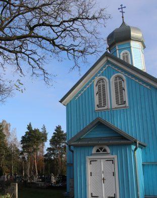 Niebieska drewniana cerkiew cmentarna w Rybołtach na tle niebieskiego nieba