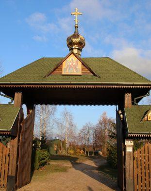 Drewniana brama główna zwieńczona krzyżem prawosławnym i ikoną prowadząca do skitu w Ordynkach